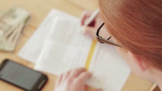 A young woman fills out a paper form at home. Top view with shallow DOF, static footage.