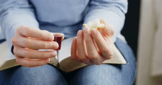A young woman holding Communion elements praying with closed eyes.