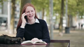 A young woman holds a book and talks on a mobile phone in a city park.