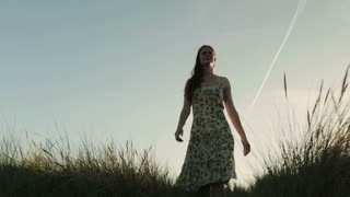 A young woman in a dress walks on beach dunes by sunset. Tracking footage.