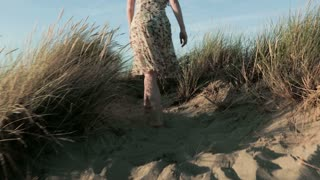 A young woman in a summer dress walks on dunes. Tracking footage.