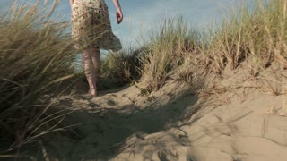 A young woman in a summer dress walks over beach dunes. Tracking footage.