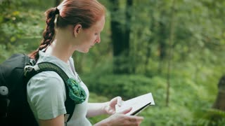 A young woman reads a map, looks around for directions in a green forest and then walks past the camera.