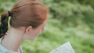 A young woman reads a paper map and looks around in a green forest by summer.