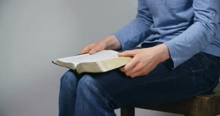 A young woman reads the Bible and prays. Medium tilt shot.