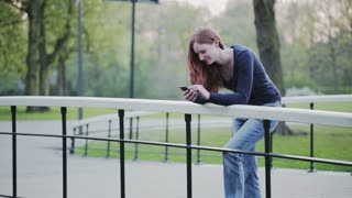 A young woman relaxes on a bridge in a city park and uses a mobile phone.