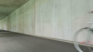 A young woman rides a city bicycle in a half open tunnel with concrete walls.