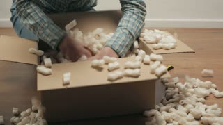 A young woman searching through an open carton box parcel, filled with insulation foam. Low angle static shot.