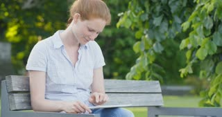 A young woman sitting on a bench in a park and using a tablet on her lap. Medium shot.