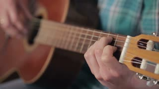A young woman strums on an acoustic guitar. Closeup shot with shallow DOF.