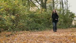 A young woman walks on a park alley covered with tree leaves. Autumn season footage.