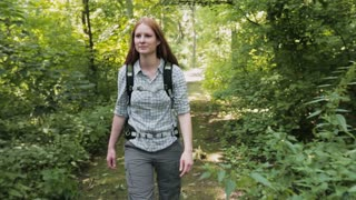 A young woman with a backpack walks through a green forest park by summer. Tracking footage.