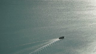 Aerial footage of a ferry boat sailing over a large lake by sunset.
