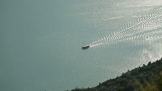Aerial footage of a ferry boat traveling on a calm lake by sunset or sunrise.
