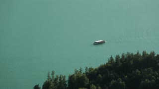 Aerial footage of a ferry boat traveling on a calm lake with green water by summer.