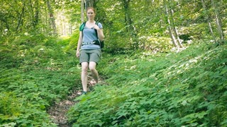 An active young woman hikes down a narrow mountain trail in a green forest by summer.