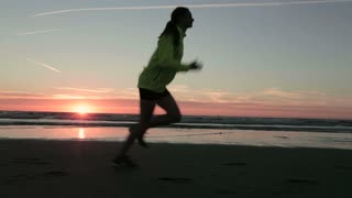 An active young woman jogging on a beach by summer.
