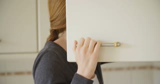 An attractive redhead young woman smiles at the camera next to an open kitchen cupboard door.