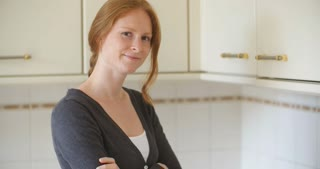An attractive redhead young woman with crossed arms smiles at the camera in a classic kitchen.