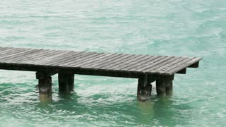 An empty old wooden dock among water waves in a green lake. Static footage.