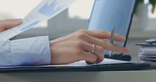 Business woman reading a document and playing anxiously with a pen in her hand. Closeup shot.