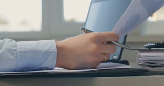 Businesswoman working at her desk - typing on laptop and reading financial documents.