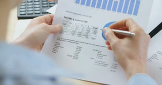 Businesswoman working with financial documents with charts and tables. Closeup over the shoulder footage.
