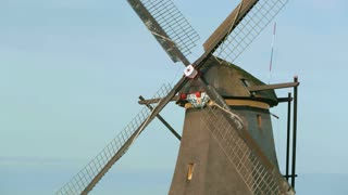 Closeup footage of a Dutch windmill spinning around.