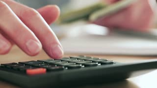 Closeup footage of a female accountant doing financial calculations with a calculator over a wooden desktop.