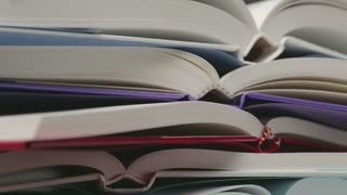 Closeup footage of a pile of open books spinning on its axis.
