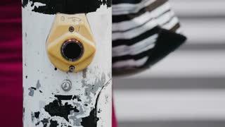 Closeup footage of a traffic light button at a pedestrian zebra crossing on a city street.