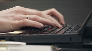 Closeup footage of a young woman typing on a computer in an office.