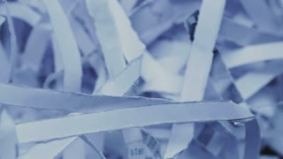 Closeup footage of destroyed or shredded confidential office documents. Dolly shot.