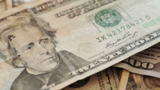 Closeup footage - the camera slides over a pile of American dollar banknotes laying flat.