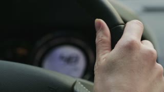 Closeup of the hand of a female driver at the steering wheel of a moving car.