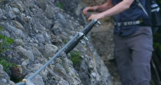 Closeup slow motion shot of a young woman hiking on a narrow mountain via ferrata (cable assisted) trail by summer.