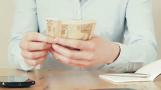 Closeup static footage of a woman counting 50 Euro bills on a desk.