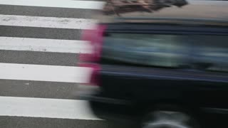 Detail footage of cars driving over a zebra crossing on a busy street.