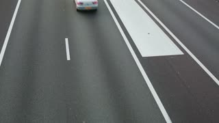 Elevated view of cars driving fast on a two lane highway with an adjacent acceleration lane.