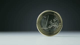 Extreme closeup footage of a one Euro coin spinning slowly on its axis.