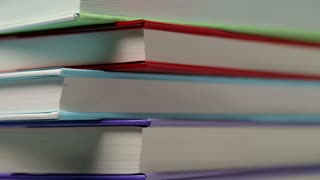 Extreme closeup footage of stacked colorful books spinning from left to right.