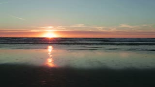 Fast moving footage of a beach sunset by summer with calm water waves.