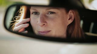 Female car driver talks on the phone. Detail footage of reflection in the rear view mirror.