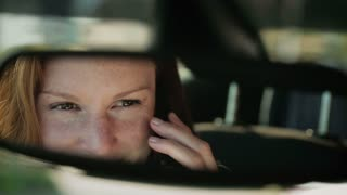 Female car driver talks on the phone, handheld. Detail footage of reflection in the rear view mirror.