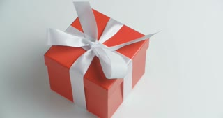 Female hands open a red gift box. Closeup shot.