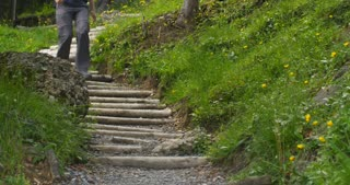 Female hiker descends stairs on a mountain trail by summer. Slow motion medium shot.