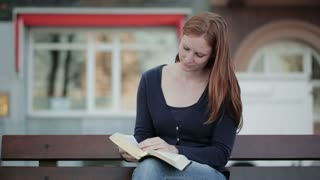 Frontal shot of a young woman sitting on a bench on a city street and reading the Bible.