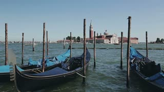 Gondolas docked on the Grand Canal in Venice, Italy and a view at the San Giorgio Maggiore island.