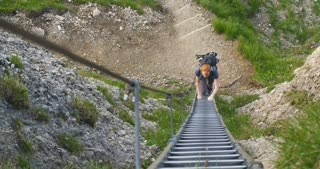 High angle view of a young woman climbing a ladder on a mountain trail by summer.