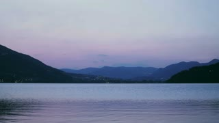 Lake Lago di Caldonazzo in Northern Italy and the surrounding mountain hills. Static footage on a summer evening.